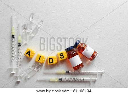 Aids word and medical equipment on light background