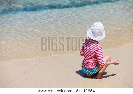 Little girl in a colorful sun protection swimwear on vacation at tropical beach