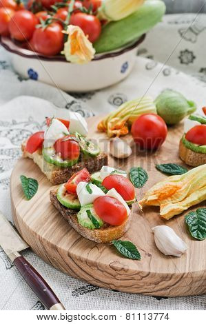 Toasted bread topped (Bruschetta) with grilled zucchini, mozzarella, cherry tomatoes. Italian cuisin
