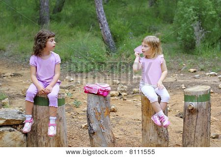 Two Little Girls Sit On Forest Park Tree Trunks