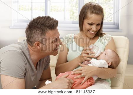 Happy mother and father smiling, looking at baby girl while feeding from bottle.