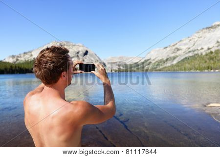 Mobile photography - man taking picture with phone. Young adult photographer holding smartphone taking pictures of nature landscape. Lake in Yosemite National Park, California, USA.