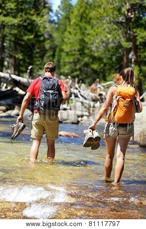 Hikers group walking barefoot crossing river in forest. Adventure people on hike hiking in nature holding shoes and boots to cross with wet feet.