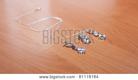 Jewelry and silver chain, on wooden desk.
