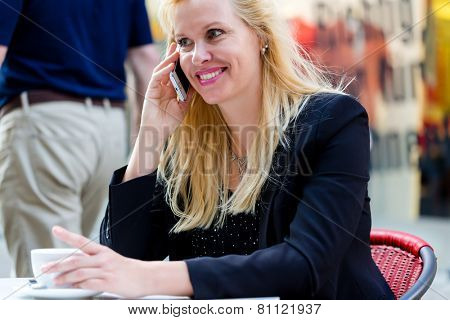 Mature woman using phone in city street cafe in front of shop window drinking cup of coffee