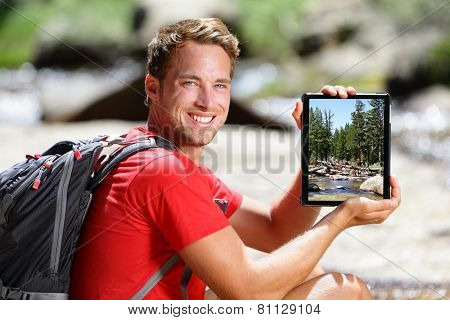 Hiking man showing nature forest picture on tablet. Young adult taking pictures with digital tablet computer of landscape in Yosemite National Park, California, USA.