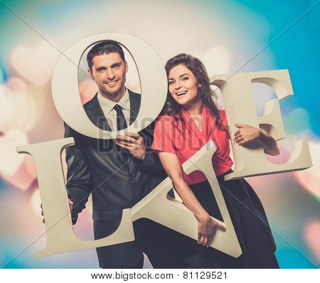 Couple holding word LOVE over blurred background