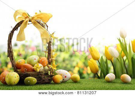 Basket of easter eggs on meadow