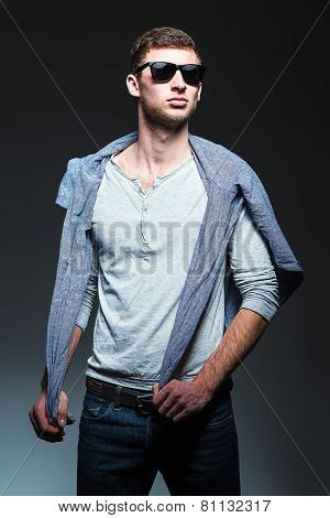 Studio Fashion Shot: Handsome Young Man Wearing Jeans, Shirt And Sunglasses