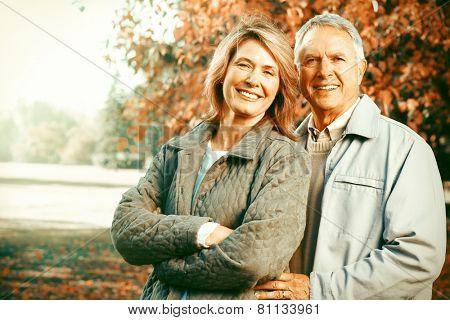 Happy senior loving couple over park nature background