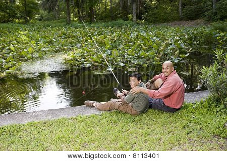 Hispanic Father And Son Fishing In Pond