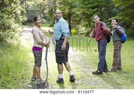 Hispanic Family Hiking In Woods On Trail