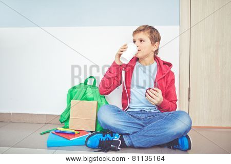 Handsome youngster having snack while sitting on the floor by classroom door