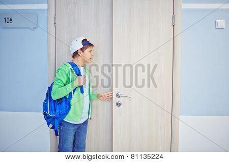 Pre-teen schoolboy opening classroom door and looking inside