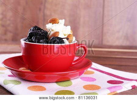 Dessert with prunes and almonds in red cup on napkin and wooden planks background