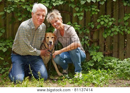 Elderly man and smiling woman sitting with their dog in a garden