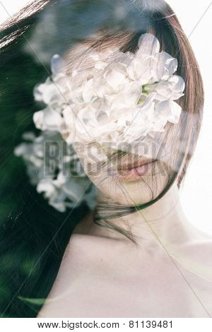 Double exposure portrait of young woman combined with photograph of white lilac flowers