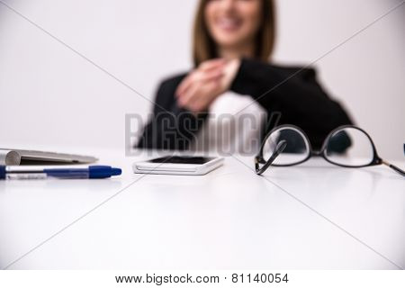 Closeup image of woman sitting at the table. Focus on table