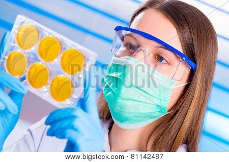 Technician with petri dishes in a medical lab