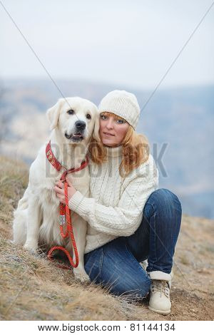 Young woman walking in the mountains with his dog.