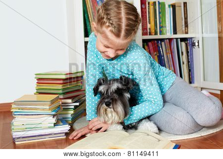 Girl And Her Dog In Glasses Reading A Book, Sitting On Floor In Library