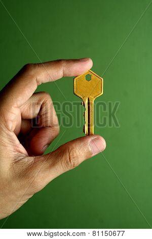 Golden key held in hand