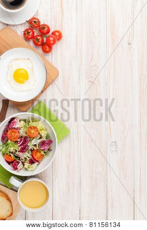 Healthy breakfast with fried egg, toasts and salad on white wooden table with copy space
