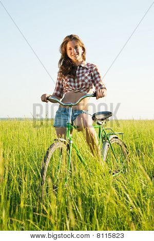Girl Riding Bicycle In  Field