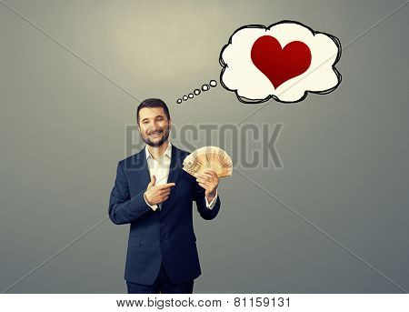 smile businessman pointing at paper money and thinking about love over grey background
