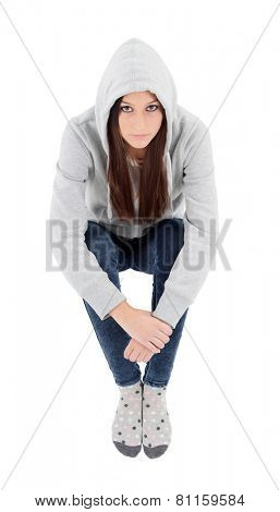 Happy hooded girl with grey sweatshirt sitting on the floor isolated
