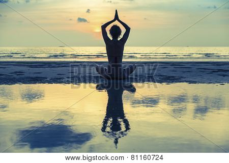 Silhouette young beautiful woman practicing yoga on the beach at surrealistic sunset.