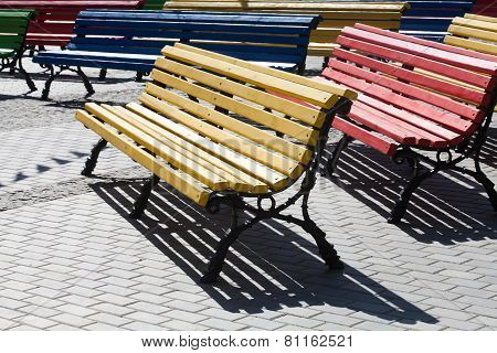 Multicolored Wooden Benches On The Fascia Tile On A Sunny Day.