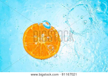 Pouring water on an organic Tangerine - top view
