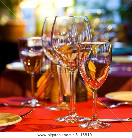 Hotel Service: Table In A Restaurant With A Red Tablecloth, Red Napkins, Wine Glasses And Cutlery.
