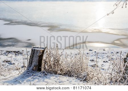 Stump on a background of a frozen river