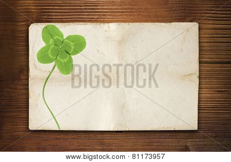 clover symbol on old wood background with empty paper