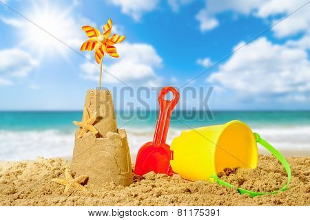 Sandcastle with bucket and spade with beach blur background