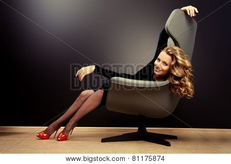 Beautiful model with long wavy hair sitting in a chair. Business, elegant businesswoman. Interior, furniture.