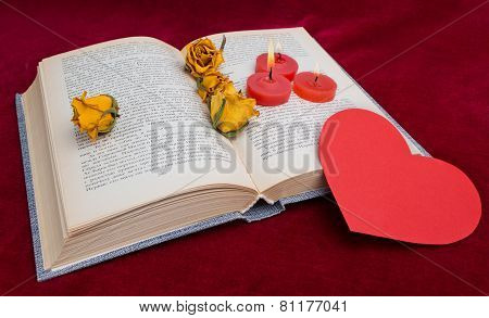 Three Red Candles Lying On The Book With Red Heart