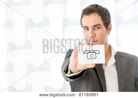 Businessman Holding A White Card With Phone Symbol With Copyspace