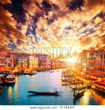 Venice, Italy. Gondola floats on Grand Canal at romantic sunset. View from Rialto Bridge