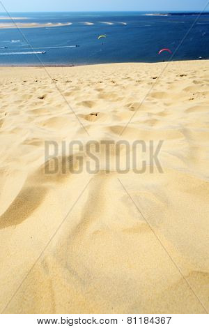 PILAT, FRANCE - JUNE 27, 2013: Parasailers and tourists on the dune of Pilat. This dune is the biggest one in Europe, and it still grows