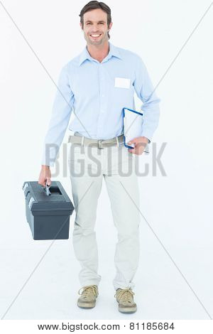 Portrait of happy supervisor carrying tool box and clipboard over white background