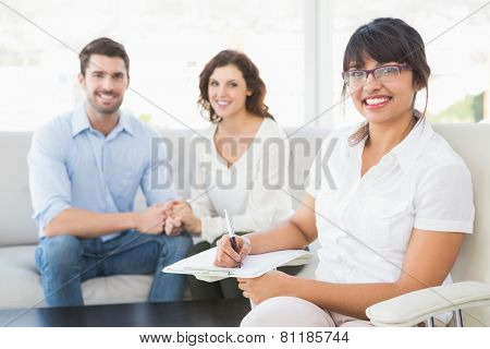Smiling therapist with patients looking at camera in the office