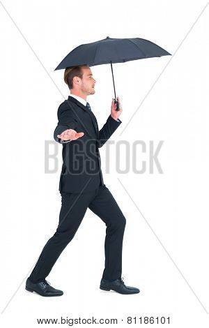 Concentrated businessman with umbrella walking on white background