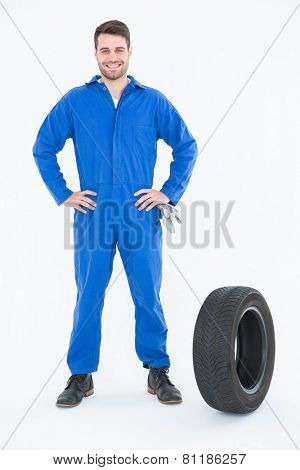 Full length portrait of smiling young male mechanic with hands on hips standing by tire on white background