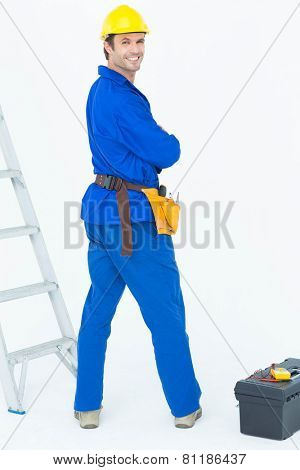 Portrait of happy electrician looking over shoulder against white background