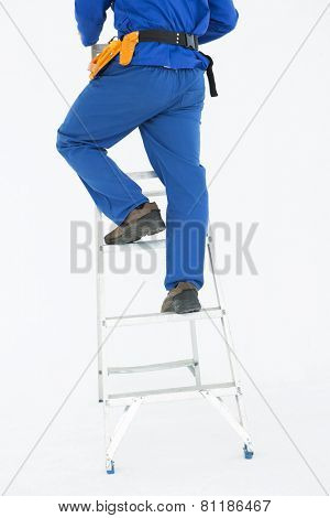 Low section of repairman climing ladder against white background