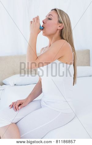 Beauty blonde using asthma inhaler at home in the bedroom