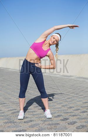 Fit blonde stretching on the pier on a sunny day